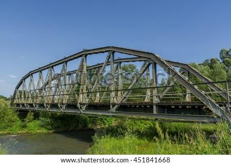 Old metal railroad bridge over the river - stock photo