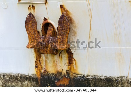 old metal rusted sea anchor on the hull of a large ship - stock photo