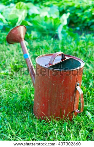 Old metal watering can garden on the bright green grass. - stock photo