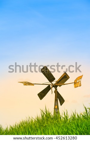 Old metal windmill with four wings at a low hill of grass at warm light with large blue colored sky (copy space)/Small Rusty Windmill - stock photo