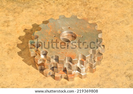 Old metallic gear wheels on dirty  concrete floor background. - stock photo