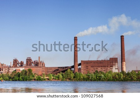 Old Metallurgical Works on the riverside. Industrial landscape - stock photo