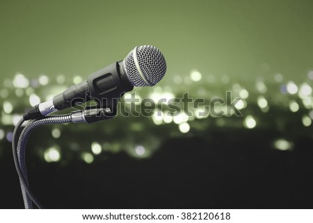 old microphone with blur light in city background