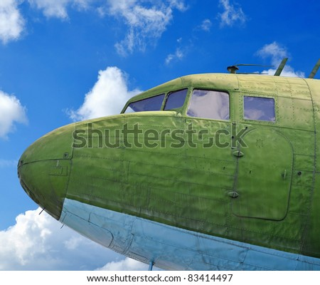 Old military aircraft nose against blue cloudy sky - stock photo
