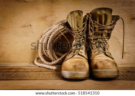 old military boots and rope on a wooden table