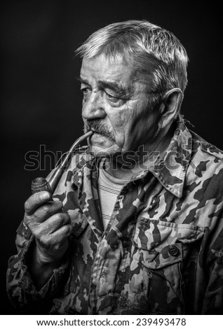 old military with glasses smoking a pipe