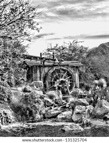 Old mill and water wheel in black and white - stock photo