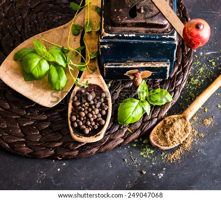 old mill and wooden spoons with spices on a black table - stock photo