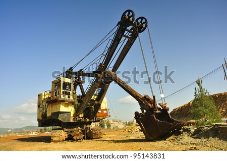 Old mining big machines backhoe - bulldozer working in old development