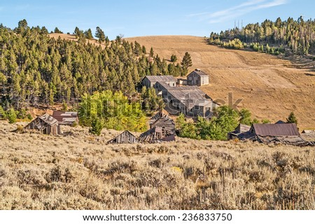 Old mining town in Montana with the oldest buildings on the side of the hill in the foreground and the newer flotation mill and bunkhouse on the other hill.  It is a ghost town now. - stock photo