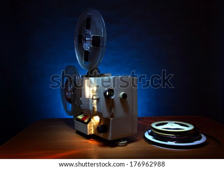 Old 8mm film projector in dusk beside a stack of film reels - stock photo