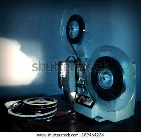 Old 8mm film projector showing the film in dusk onto a wall beside a stack of film reels - stock photo