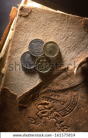 Old money. United Kingdom pre-decimal 1971 currency. Pounds, shillings and pence on old damaged bible book stamped with the  price, two shillings and six pence. - stock photo