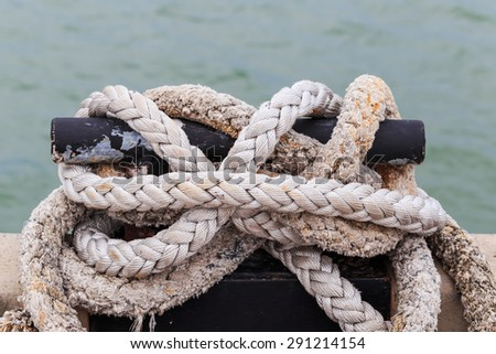 old Mooring Bollard with rope tied on pier by the sea nature background - stock photo