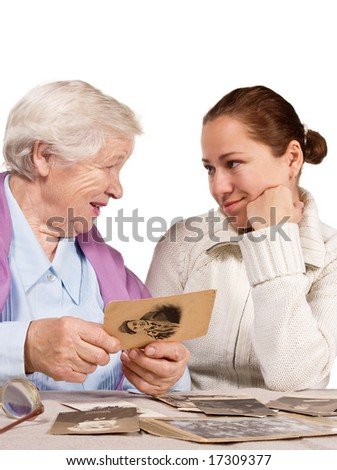 Old mother and her adult daughter sitting together and looking at very old photo