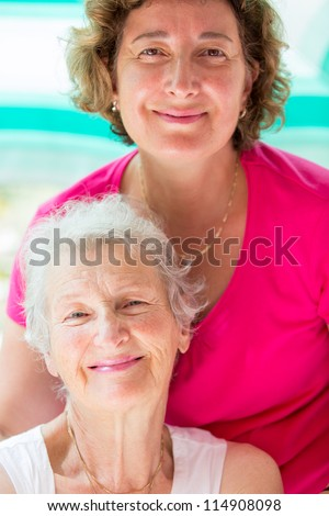 Old mother and her daughter posing with satisfied look. - stock photo