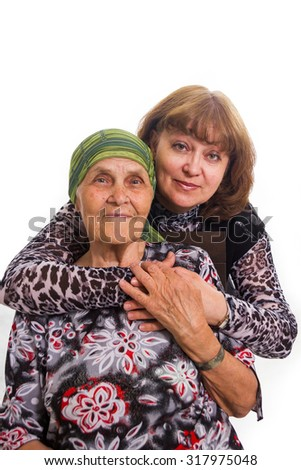 Old mother and the adult daughter in love to care, having embraced - stock photo