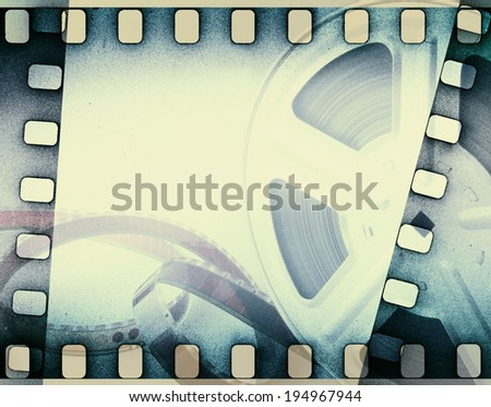 Old motion picture film reel with film strip. Vintage background - stock photo
