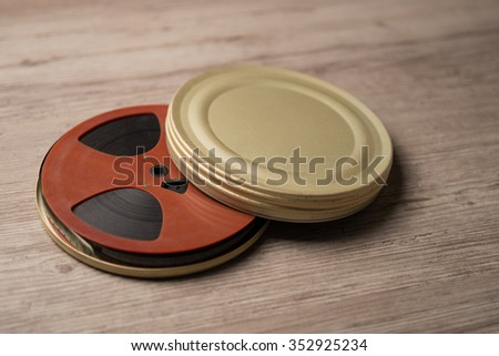 Old motion picture film reel with golden can - stock photo