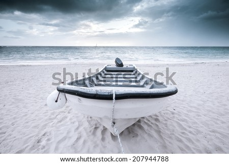 Old motor boat on a tropical beach with stormy cloudy skies. Neutral and airy nautical background. Fashion, water sports, transportation and travel concept. - stock photo