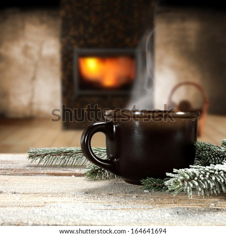 old mug of hot drink and fireplace  - stock photo