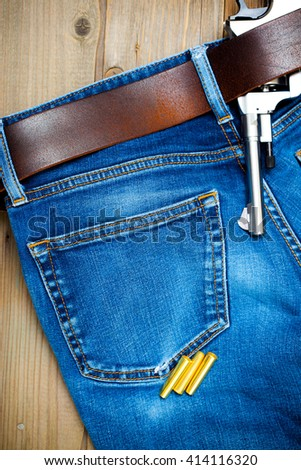 old nagan in his belt of blue jeans - stock photo