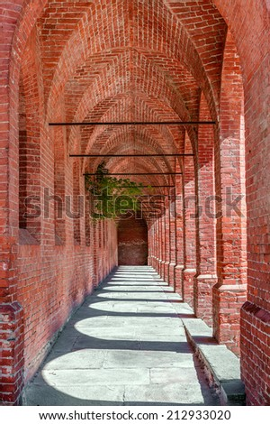 Old narrow brick arcade in town of Pollenzo in Piedmont, Northern Italy. - stock photo