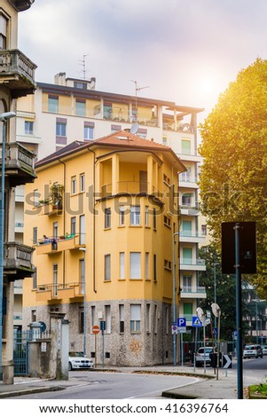 Old narrow house yellow color in the city of Novara. Italy. Toning - stock photo