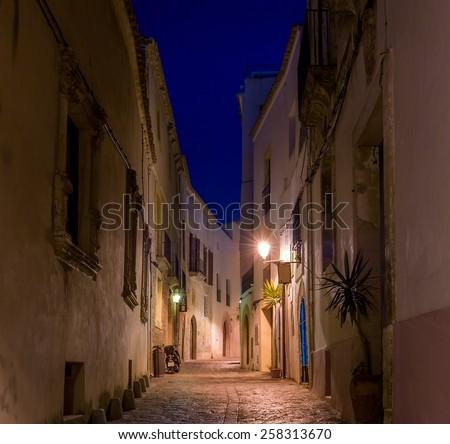 Old narrow street with lanterns night photo. Ibiza old town. Spain - stock photo