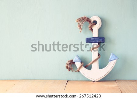 old nautical anchor on wooden table over wooden aqua background  - stock photo