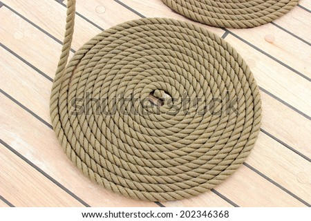Old nautical thick rope wrapped in spiral lying on weathered deck of yacht, circle of thick rope - stock photo