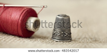 Old needle, thread and thimble - website banner of hobby, hand-made concept