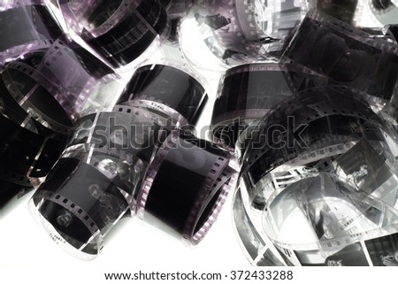 Old negative 35 mm film strip on white background, strip of tangled movie film - place for copy and space text - stock photo