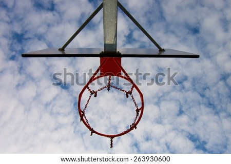Old neglect basketball backboard with rusty hoop above street court. Blue cloudy sky in background.  - stock photo