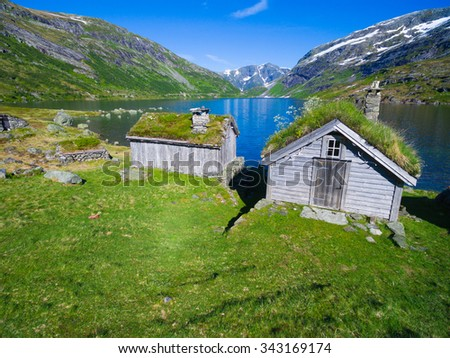 Old norwegian huts by picturesque lake surrounded by mountains in Gaularfjellet mountain pass in Norway - stock photo
