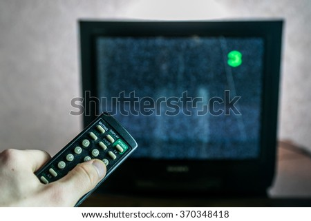Old not working TV with noise and remote control - stock photo