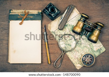 Old notebook, compass, map, vintage binoculars, pen and inkwell, pocket knife, magnifying glass on wooden background - stock photo
