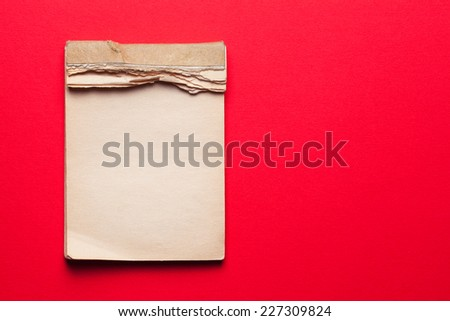 old notebook on red background  - stock photo