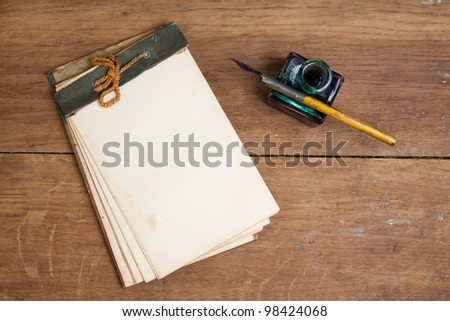 Old notepad, ink pen and inkwell on wood background - stock photo