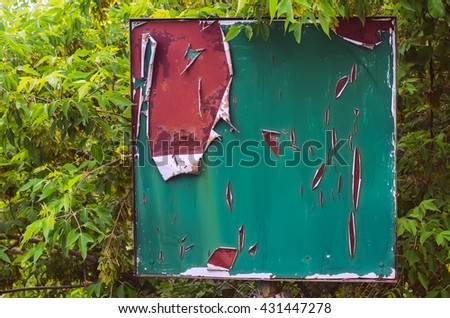 Old notice board, standing on a street among the foliage. - stock photo