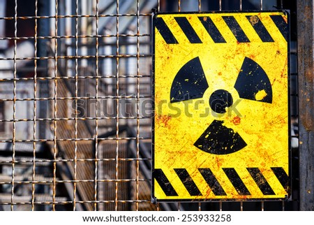 old nuclear warning sign at a fence - stock photo