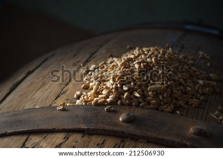 Old oak barrel on a wooden table. Behind blurred dark  - stock photo
