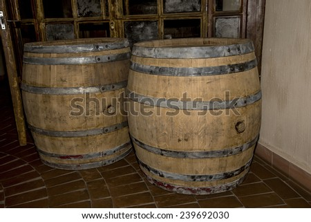 Old oak barrels in the cellar at the entrance to the dark background of the old glass door with broken glass walls in dark colors - stock photo