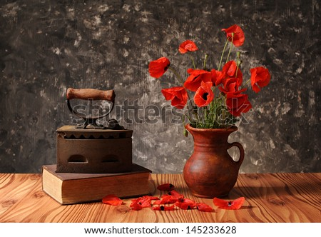 Old of books and flowers in a vase on the table - stock photo