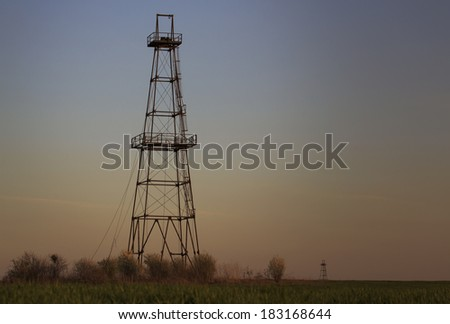 Old oil and gas rig structure, profiled on sky, under evening natural light