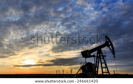 Old oil and gas well pump silhouette, profiled on sunset sky - stock photo