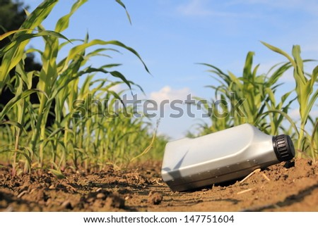 Old oil can wasting a cornfield - stock photo