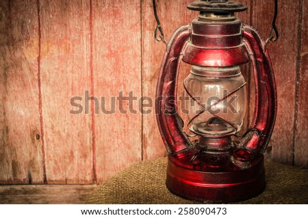 Old oil Lamp on a wooden backgrounds in vintage,retro tone.