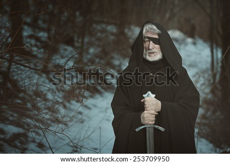 Old one eyed man with sword in a dark forest . Fantasy and mythology - stock photo