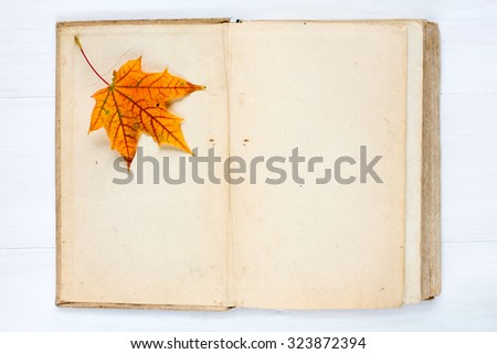 Old open book and autumn maple leaf - stock photo